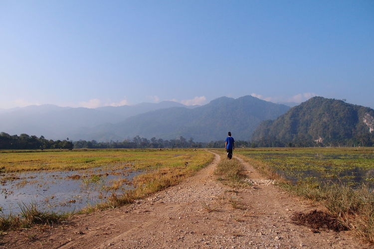 Rear view of man walking on dirt road leading towards mountains against blue sky