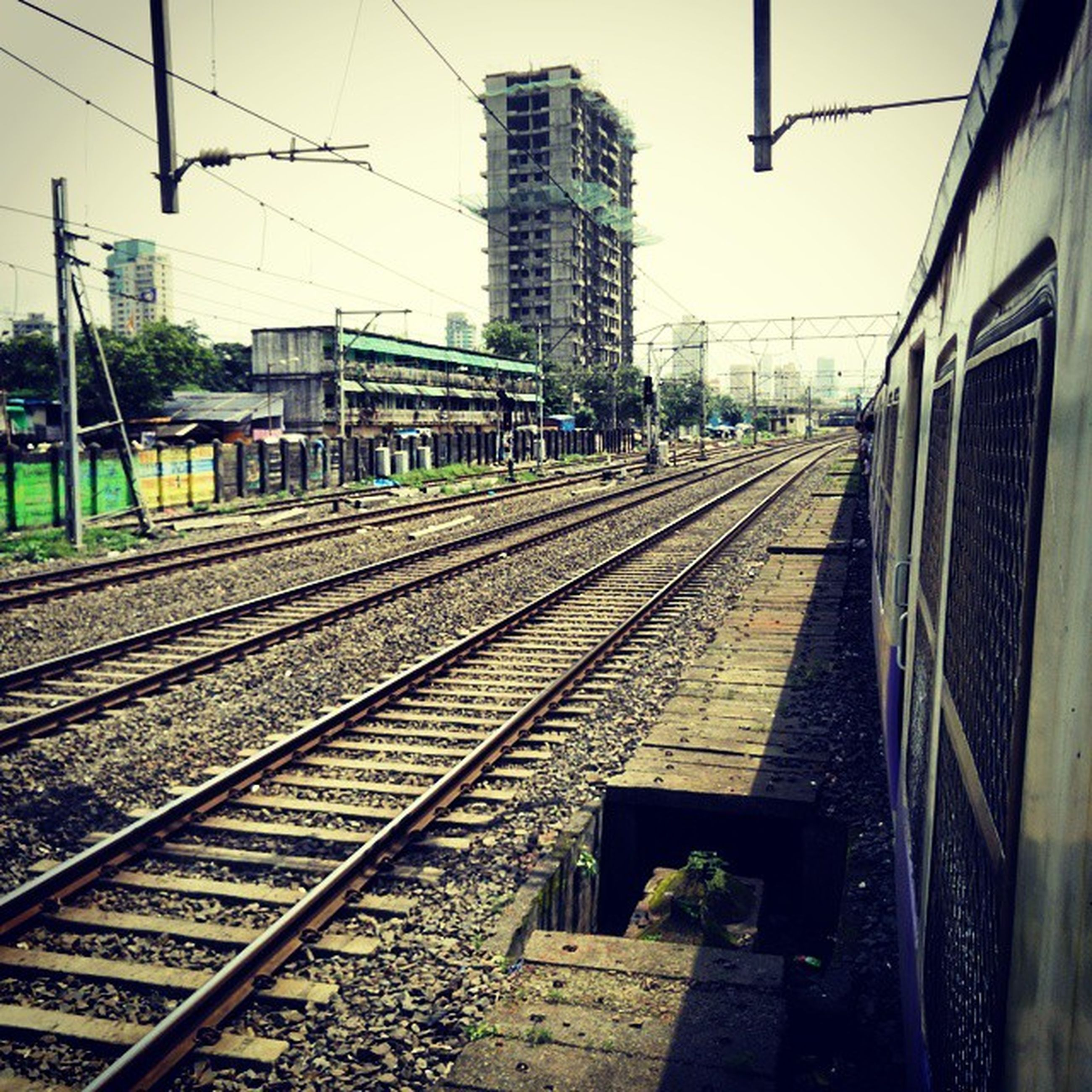 railroad track, rail transportation, public transportation, transportation, railroad station platform, railroad station, built structure, building exterior, architecture, railway track, train - vehicle, the way forward, diminishing perspective, clear sky, power line, city, vanishing point, train, day, public transport