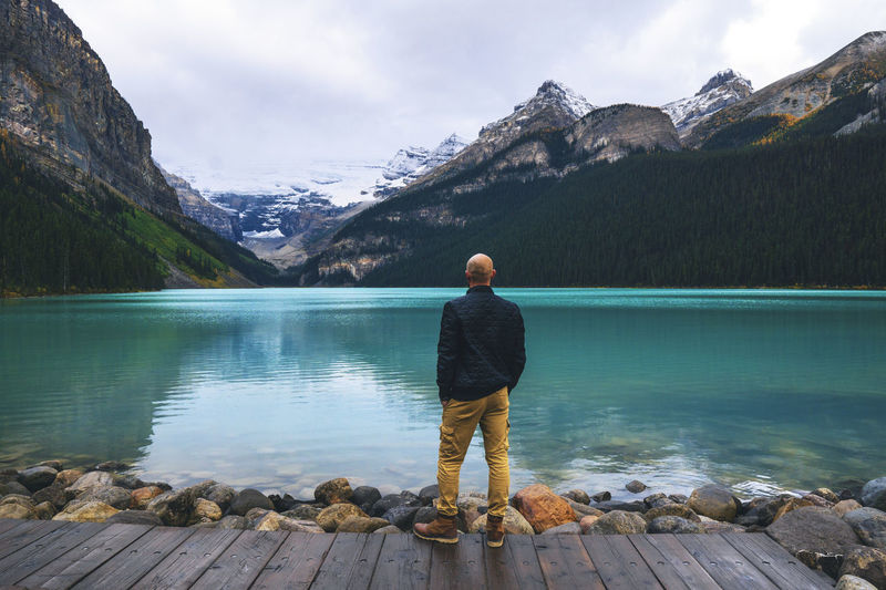 Rear view of man standing on jetty looking at lake and mountains