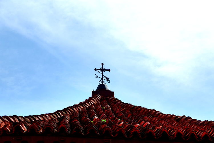 Low angle view of weather vane against building