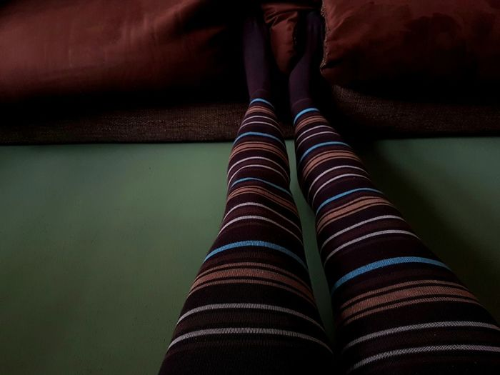 Low section of woman wearing leggings at home