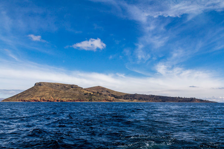 Photograph of the whole Amantani island from the point of view of a boat on the waters of Lake Titicaca, Puno, Peru. The sky and the water are blue and it is also possible to see clouds in the sky, trees and houses on the island and waves in the water. Adventure Amantaní Blue Calm Cloud Color Colorful Enjoy Hike Neighborhood Map Inca Island Lake Landscape Mountain Peaceful Peru Puno Sky Titicaca Tranquility Travel Tree Water Wave