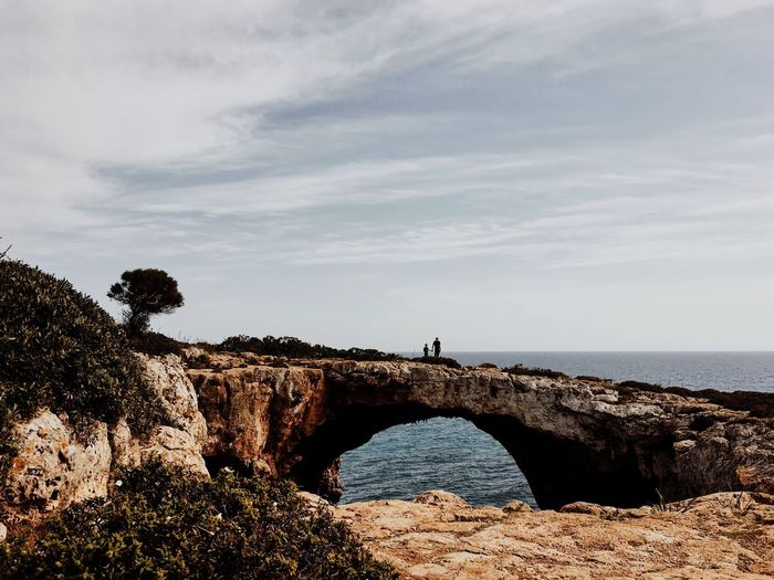 Puente Natural, Mallorca Sky Sea Nature Tranquility Real People Stone Bridge Cala Varques Hiking Natural Bridge  Climbing Bay Mallorcaisland Mallorcaphotographer Scenics Wanderlust Water Beauty In Nature Tranquil Scene Outdoors Standing Cloud - Sky Day One Person Horizon Over Water People