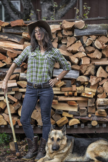Portrait of woman with dog standing against log
