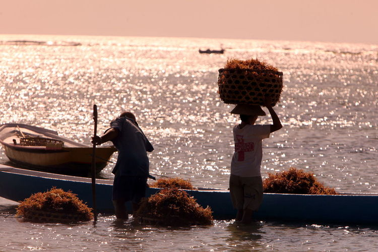 Worker carrying whicker basket by boat in sea on sunny day