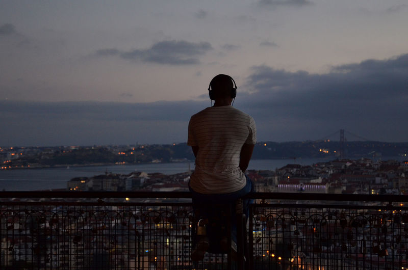 Rear View Of Man Listening Music While Sitting On Railing By Cityscape Against Cloudy Sky At Dusk