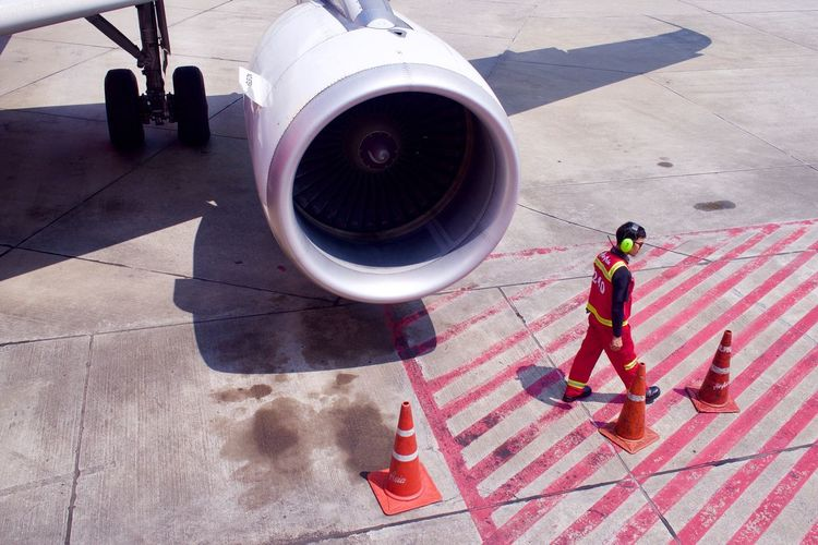 High angle view of man walking by airplane engine at runway