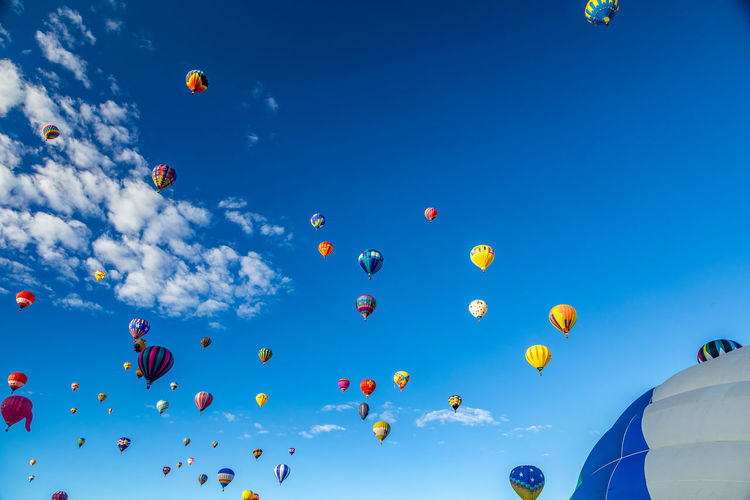 Hot Air Balloons fly over the city of Albuquerque, New Mexico during the mass ascension at the annual International Hot Air Balloon Fiesta in October, 2016 Balloon Ballooning Festival Blue Celebration Cloud - Sky Day Flying Hot Air Balloon Large Group Of Objects Low Angle View Mid-air Multi Colored No People Outdoors Sky