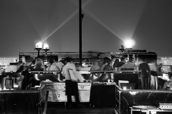 Ghosts in Restaurant Black & White Roof Terrace Bar Black And White Photography Blackandwhite Illuminated Large Group Of People Leisure Activity Lifestyles Men Night Occupation People Real People Restaurant Spotlight Spotlights Standing Women Black And White Friday