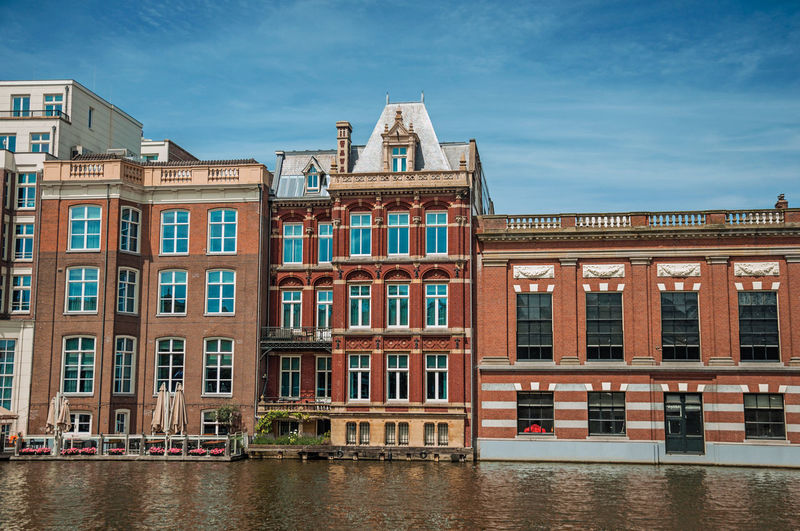 Brick buildings facade on the canal in amsterdam. the netherland capital full of canals.