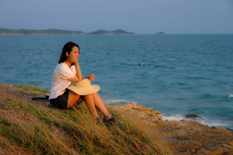 Side view of thoughtful woman sitting at beach