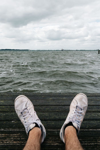 Sneakers on the pier with sea on background Adventure Close-up Cloud - Sky Day Edge Horizon Over Water Human Body Part Human Leg Low Section Men Nature One Man Only One Person Outdoors People Pier POV Shoe Sitting Sky Sneakers Standing Water