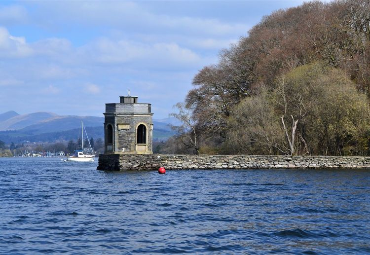 Stone built hexagonal tower on the shore of Lake Windermere, Cumbria, UK Water Architecture Tree Waterfront Built Structure Sky Plant Day Transportation Nature Cloud - Sky Mountain Beauty In Nature Scenics - Nature Nautical Vessel Arch Lake Travel Destinations Building Exterior Outdoors Bridge - Man Made Structure No People Windermere Cumbria Stone Buildings Tower Hexagonal