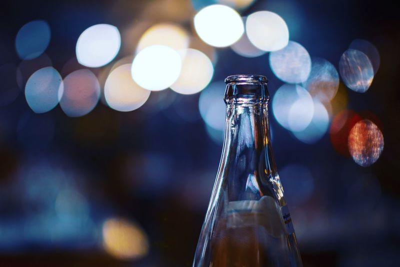 Indoors  Close-up No People Focus On Foreground Bottle Motion Glass - Material Still Life Lens Flare Container Transparent Illuminated Refreshment Water Selective Focus Night Defocused Food And Drink