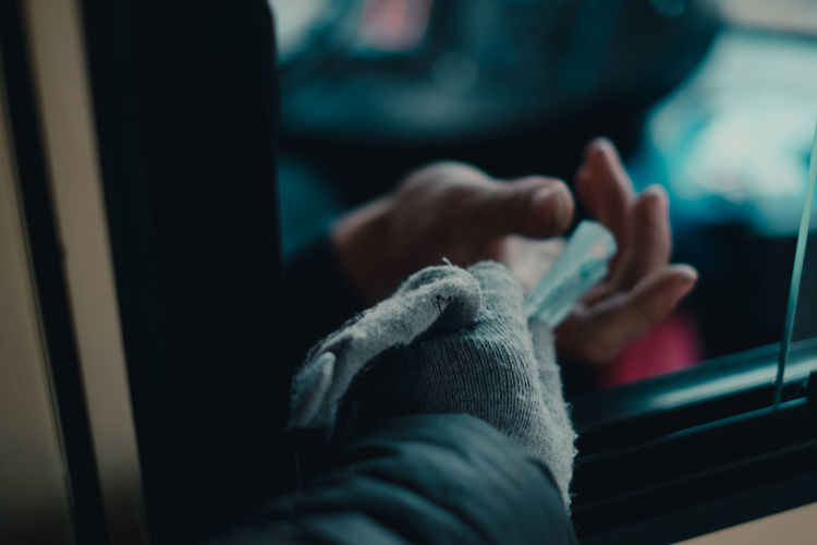 Cropped hand of person giving money through car window