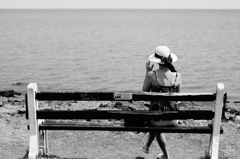 Rear view of woman sitting on bench looking at sea