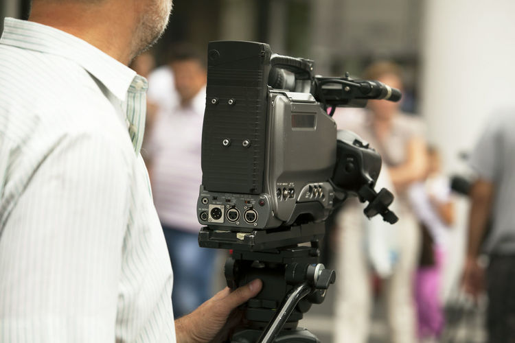 Midsection of cameraman filming with movie camera