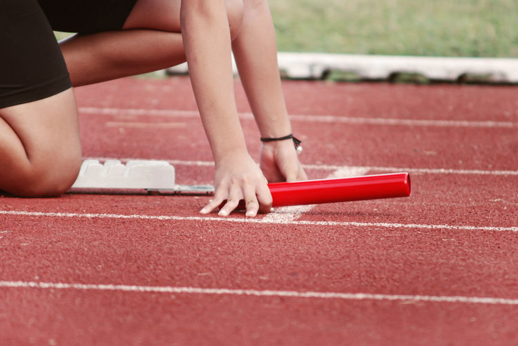 Midsection of woman crouching at starting line of running track