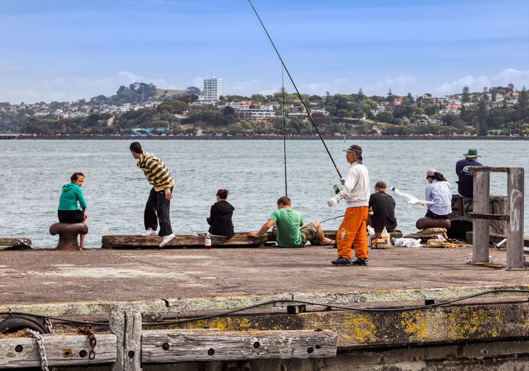 People fishing on jetty in Auckland, New Zealand. Adult Angler Angles Angling Auckland Bonding Building Casual Caucasian Cityscape Coastline Exterior Fisher Fisherman Fishing Full Length Holding Jetty Landing Leisure Lifestyle Man Nautical New Zealand North Island Outdoors Patience People Quay Rear View Rod Sea Sitting Stage Standing Stone Summer Teenager Togetherness TOWNSCAPE Travel Destinations Vacation Vessel Waist Up Waiting Water Weathered Weekend Woman Wood Group Of People Real People Built Structure Sky Day Men Women Leisure Activity Lifestyles