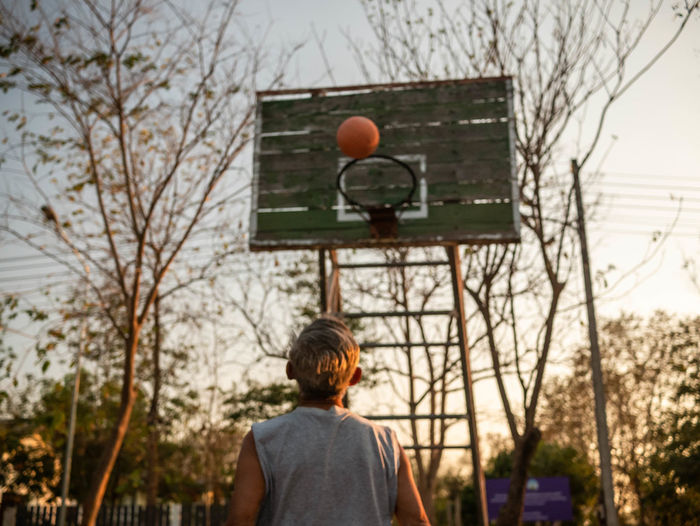 Rear view of man with basketball hoop