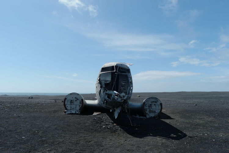 Abandoned truck on beach against sky