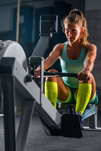 Full Length Of Woman Exercising In Gym