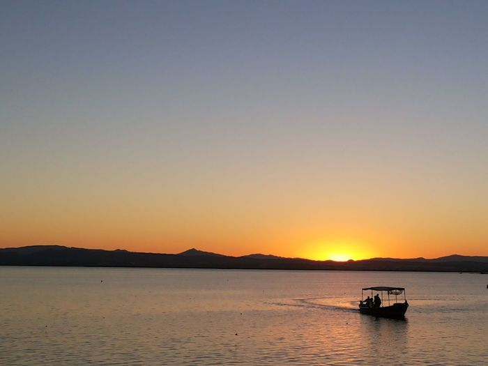 Silhouette boat in river against clear sky during sunset