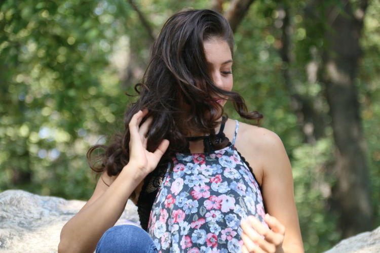 Beautiful young woman with hand in hair sitting on rocks against trees
