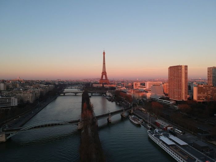 Bridge over river in city against sky during sunset paris eiffel tower drone
