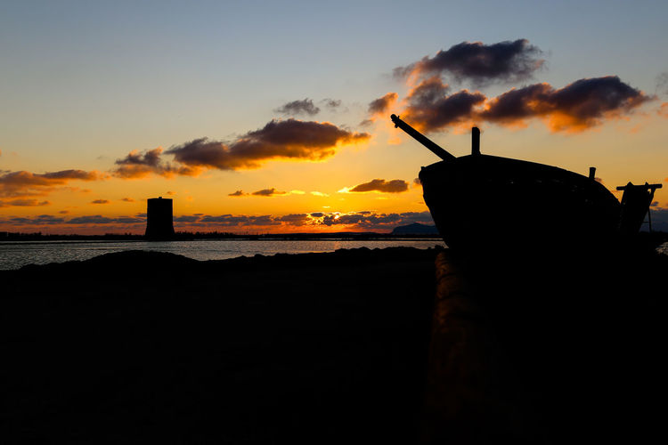 Silhouette sailboat by sea against sky during sunset