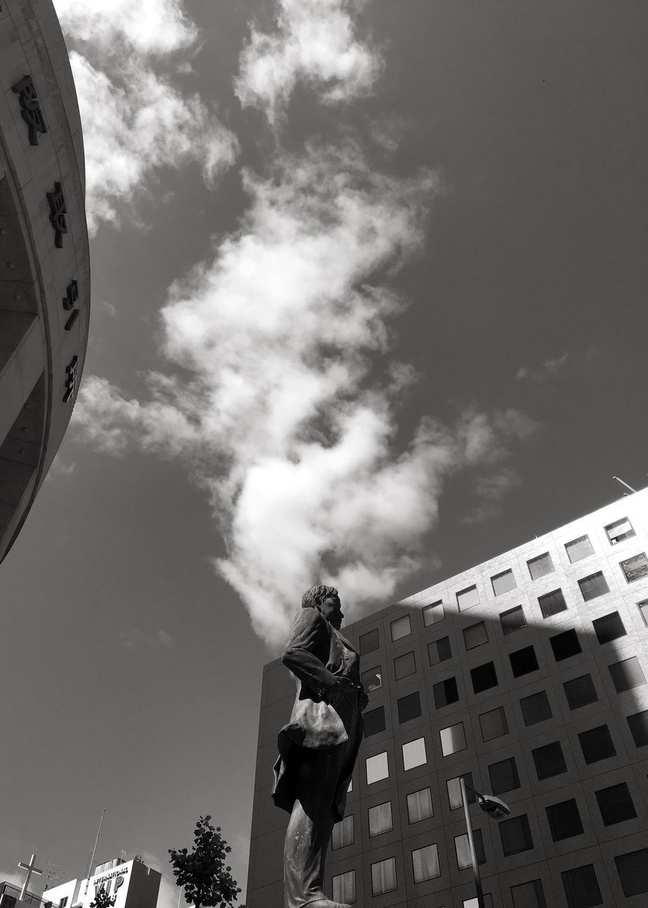 real people, low angle view, sky, cloud - sky, men, day, outdoors, one person, standing, lifestyles, building exterior, architecture, city, adult, people