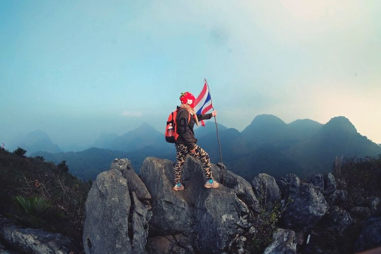 Full length of woman with thai flag standing on rocks against sky