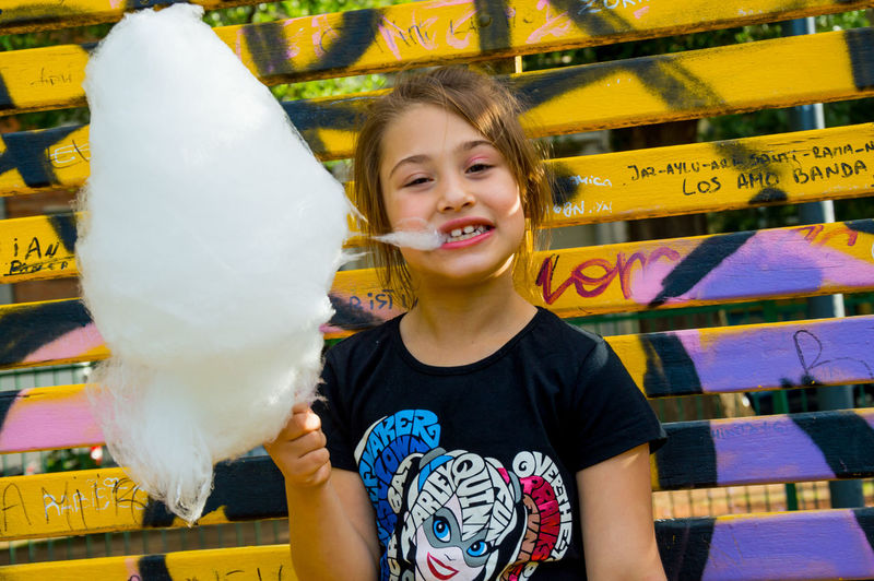 Portrait of girl eating cotton candy while standing outdoors
