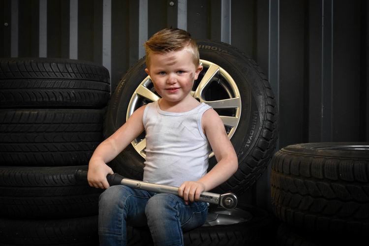 Portrait of cute boy sitting on tire at auto repair shop
