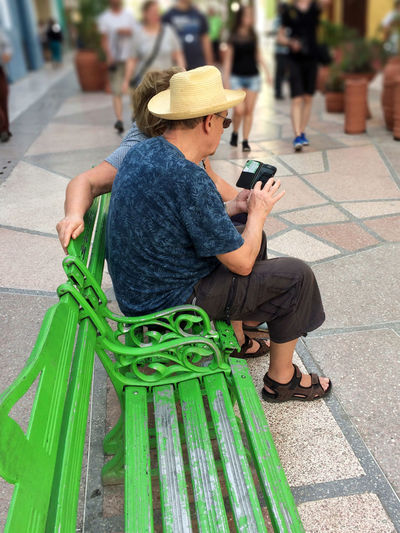 Un mundo entre las manos Bench Communication Connection Day Green Hat Mobile Conversations Old Person Outdoors People People And Places Portable Information Device Real People Smart Phone Technology Wireless Technology Women