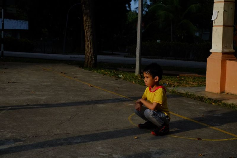 Streetphotography Street Photography Child One Person Real People Childhood Males  Sitting Boys Road Casual Clothing Leisure Activity Full Length Lifestyles Tree Plant Outdoors Innocence Street