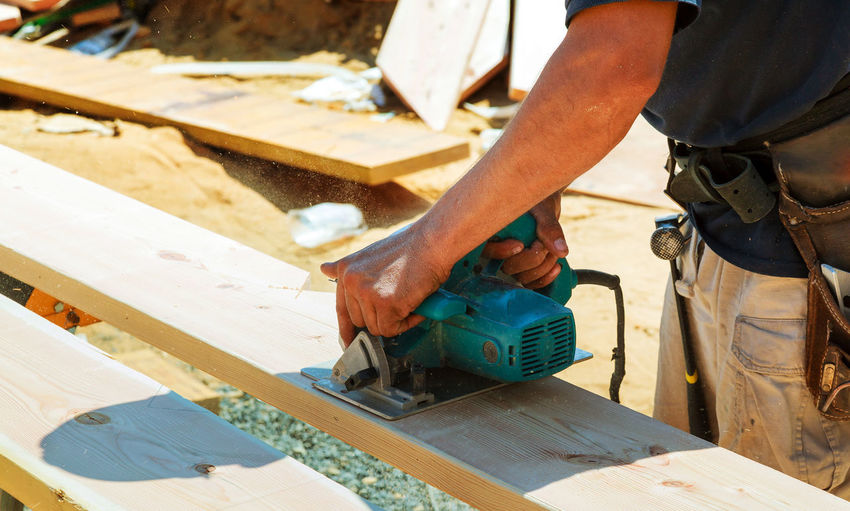 Midsection of carpenter cutting wood at construction site