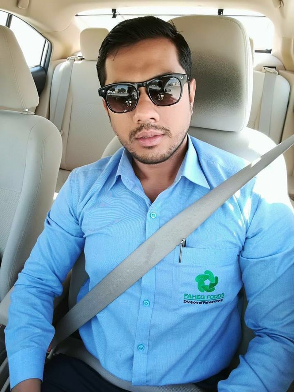 sunglasses, car, vehicle interior, land vehicle, young adult, transportation, young men, one person, mode of transport, car interior, front view, sitting, real people, lifestyles, casual clothing, looking at camera, leisure activity, day, eyeglasses, vehicle seat, portrait, outdoors