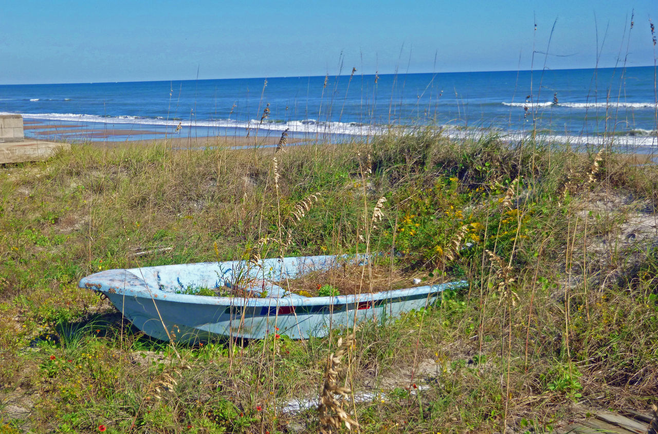 sea, grass, water, horizon over water, beach, nature, tranquil scene, day, outdoors, tranquility, scenics, no people, beauty in nature, sand, nautical vessel, sky