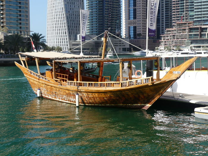 Dhow on the Marina, Dubai, United Arab Emirates 2019 Dubai UAE 2019 Marina Dhow Water Nautical Vessel Transportation Mode Of Transportation Waterfront City No People Sea Travel Moored Boat Ripples In The Water Glassy Water Palm Trees Blue Sky Sunlight And Shade Wooden Boat Traditional Dhow Tourist Attraction  Outdoor Photography