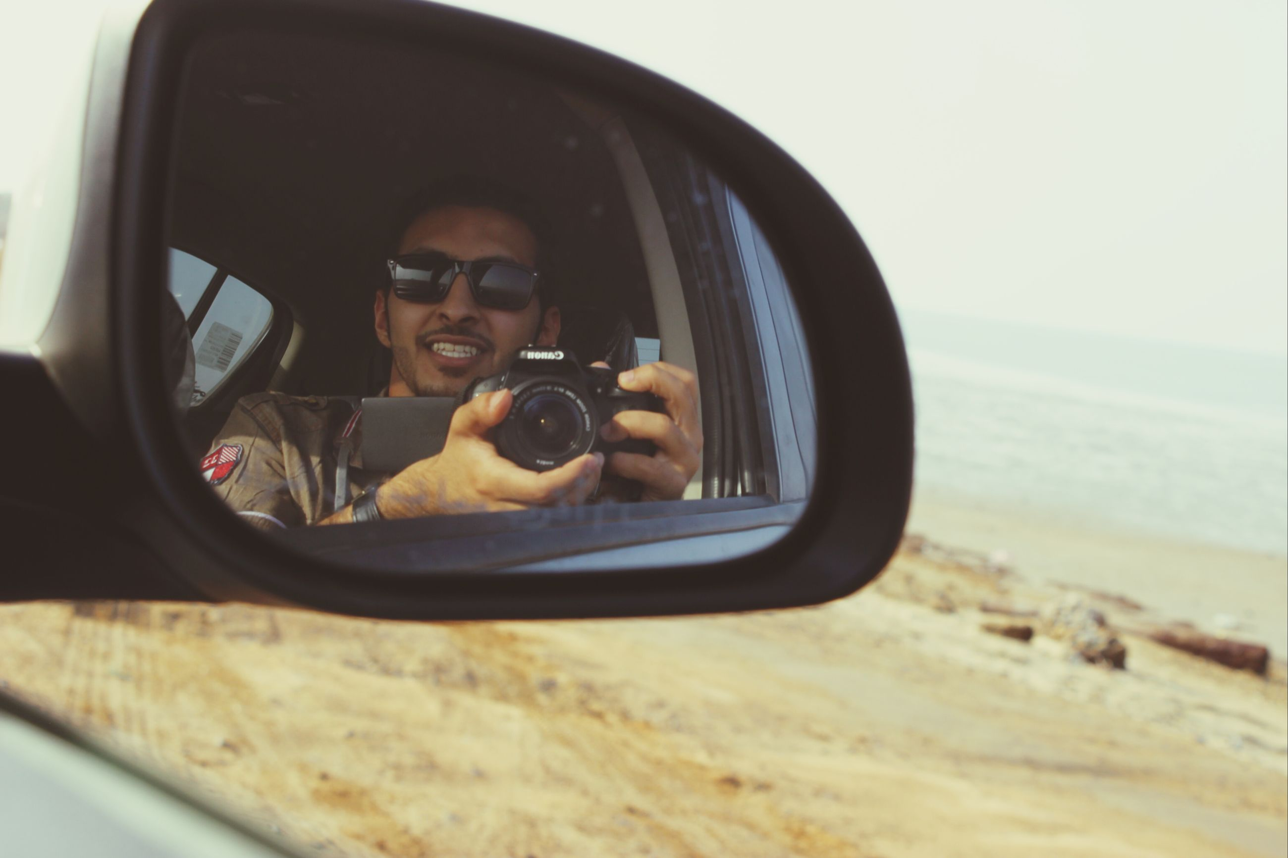 lifestyles, sunglasses, young adult, leisure activity, transportation, mode of transport, person, looking at camera, land vehicle, portrait, sitting, car, young men, travel, reflection, photography themes, front view