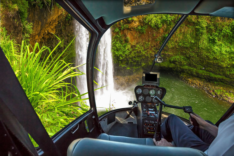 Midsection of man in helicopter against waterfall