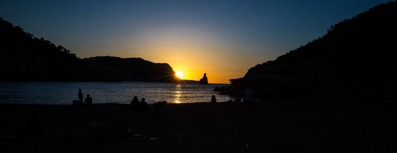 Benirrás Beach Cala De Benirràs Es Cap Bernat Ibiza, Spain Beach Beauty In Nature Group Of People Land Leisure Activity Lifestyles Nature Orange Color Outdoors Scenics - Nature Sea Silhouette Sky Sun Sunset The Finger Of God Tranquil Scene Tranquility Water Idyllic Calm Coast