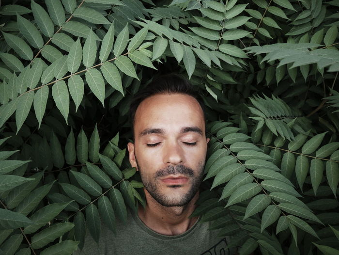 Man with eyes closed by plants