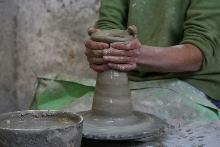 Midsection Of Male Potter Making Pot At Workshop