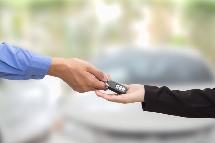 Cropped hand of male salesman giving car keys to female customer