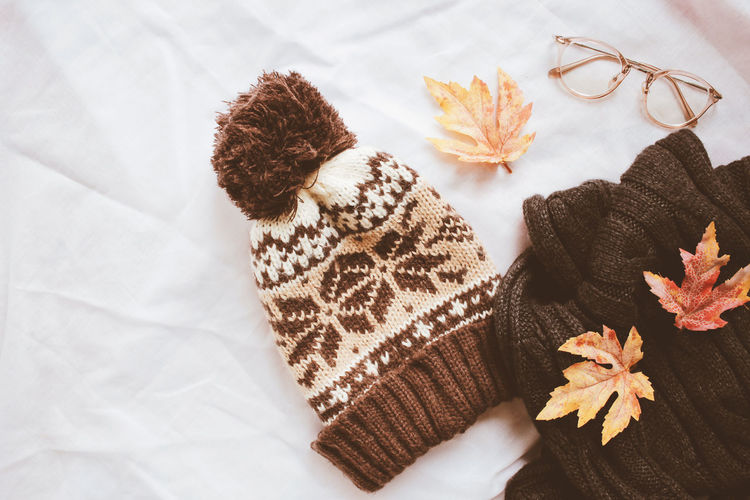 High Angle View Of Warm Clothing With Eyeglasses And Autumn Leaves On Bed