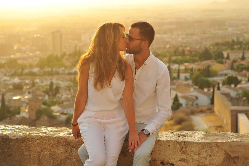 Young Romantic Couple Kissing While Sitting On Retaining Wall Against Cityscape