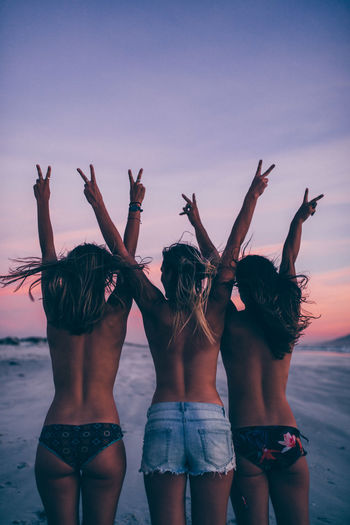 Topless Female Friends With Arms Raised Gesturing Peace Sign While Standing At Beach During Sunset