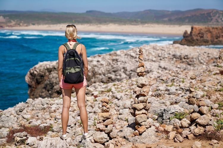 Rear view of woman with backpack looking at sea during sunny day